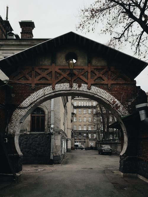 Shabby archway leading to courtyard with old buildings