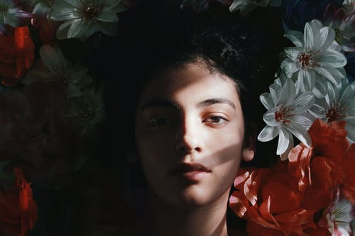 Selective Focus Photography of Woman Lying on Flowers