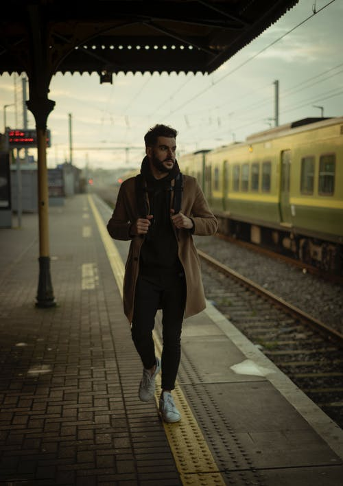 Man Wearing Brown Coat Walking Near Train Station