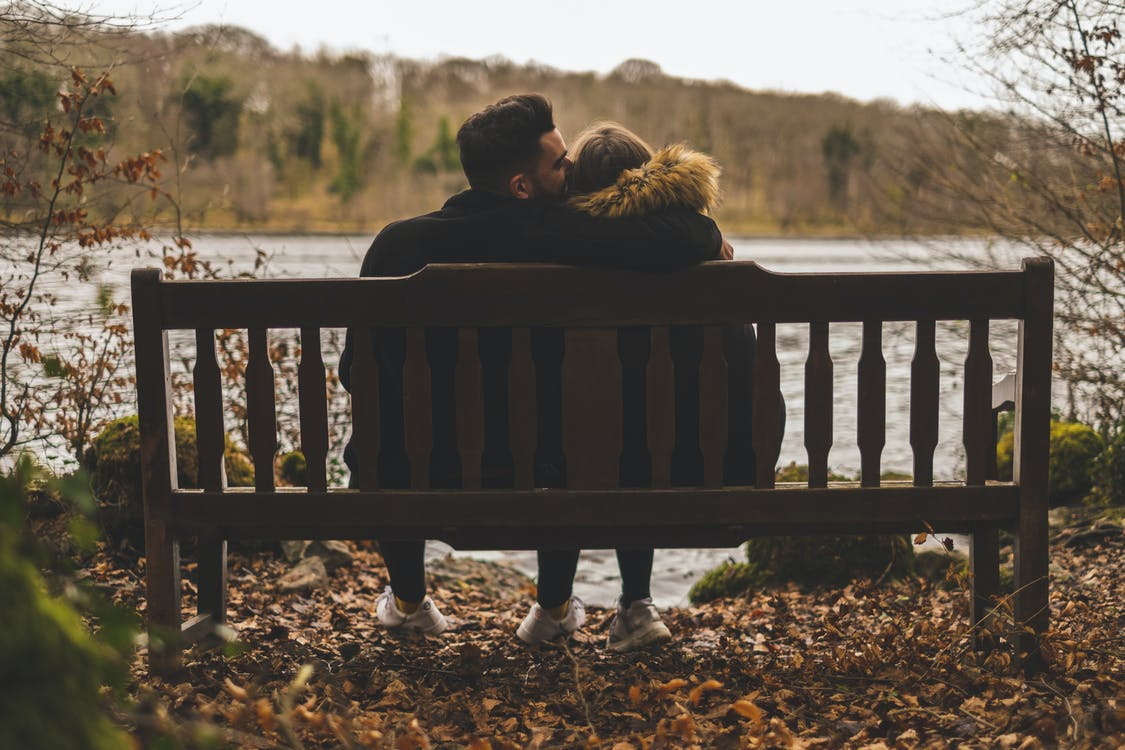 Man Kissing Woman's Head While Sitting on Bench in Front of Body of Water