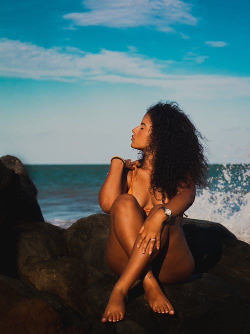Woman Sitting on Grey Rock