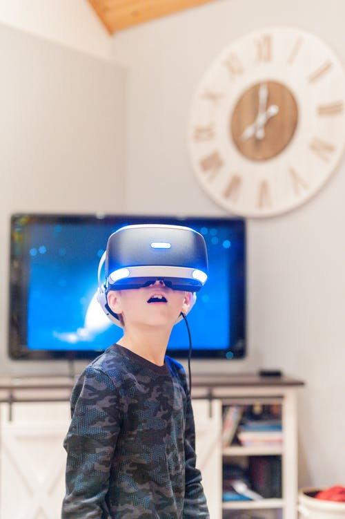 Little kid wearing virtual reality headset while playing at home