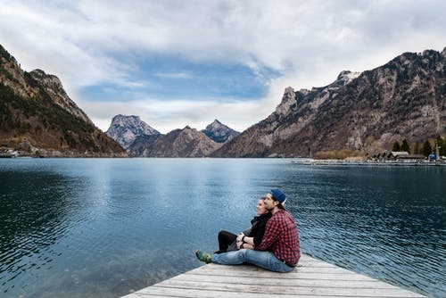Man and Woman Sitting on Brown Wooden Dock