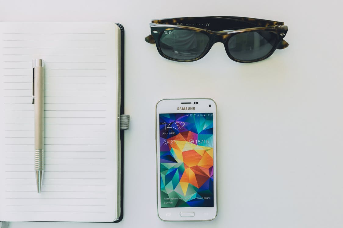 White Samsung Smartphone Beside Sunglasses,pen and White Notebook