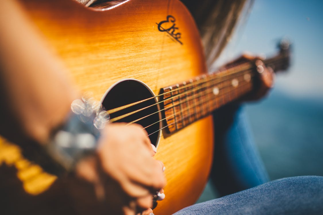 Person Play Guitar in Close-up Photo