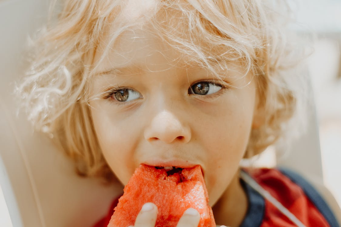 Close-Up Photo Of Boy Eating Watermelon