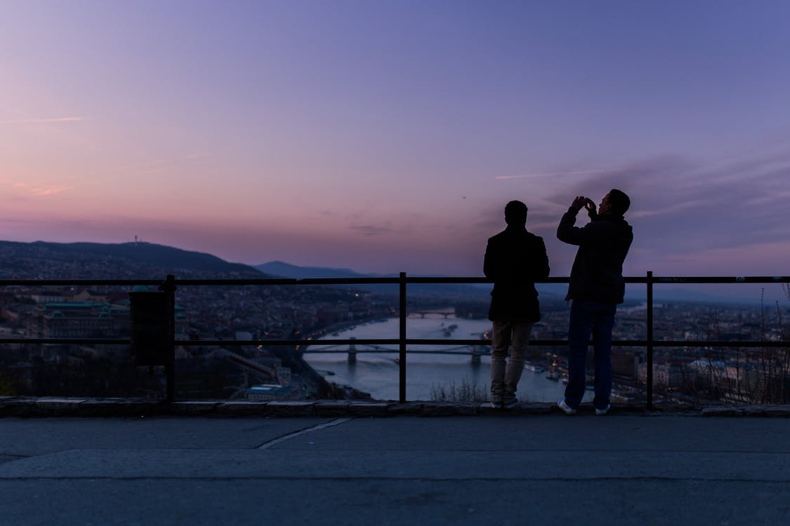 Two Person Standing Taking Picture Facing Mountain and City during Golden Hour