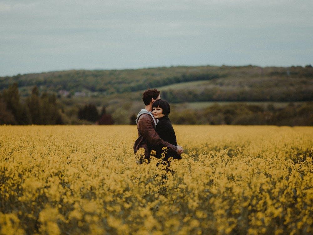 Pareja Abrazándose En Medio Del Campo De Flores