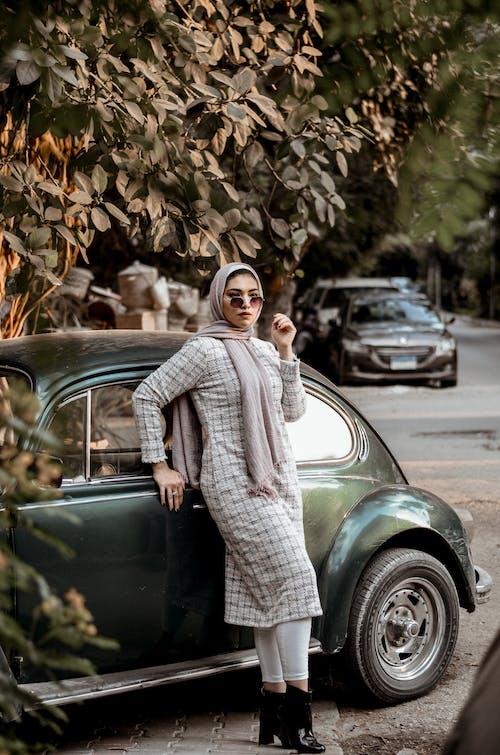 Woman Wearing Grey Long-sleeved Dress Leaning on Black Volkswagen Beetle