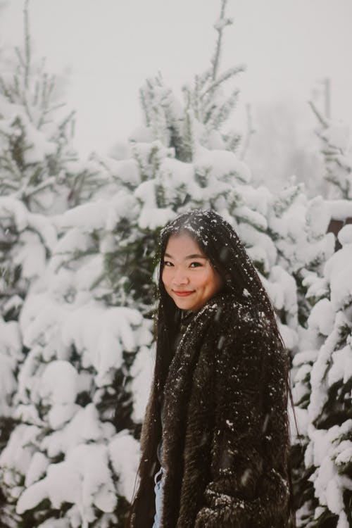Woman Wearing Black Winter Standing Near Snow-covered Trees
