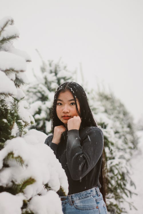 Selective Focus Photography of Woman Standing Beside Snow-covered Trees
