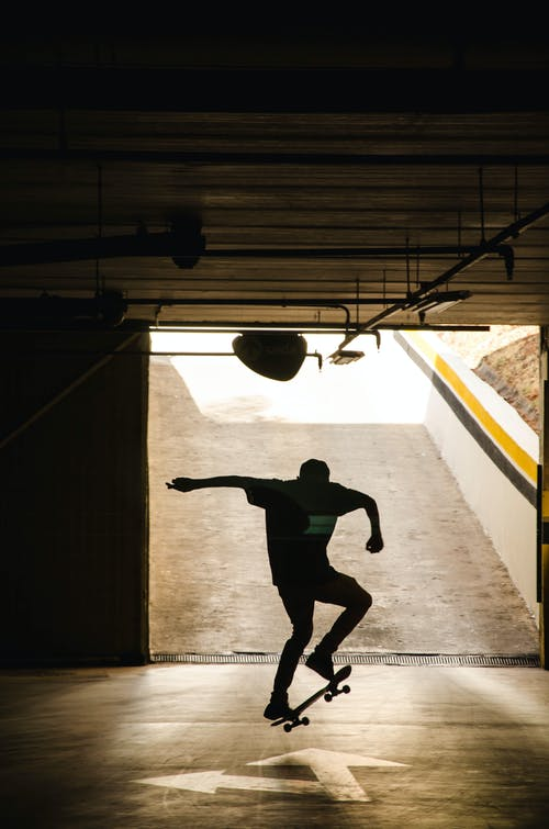 Silhouette of Man Doing Skateboard Trick