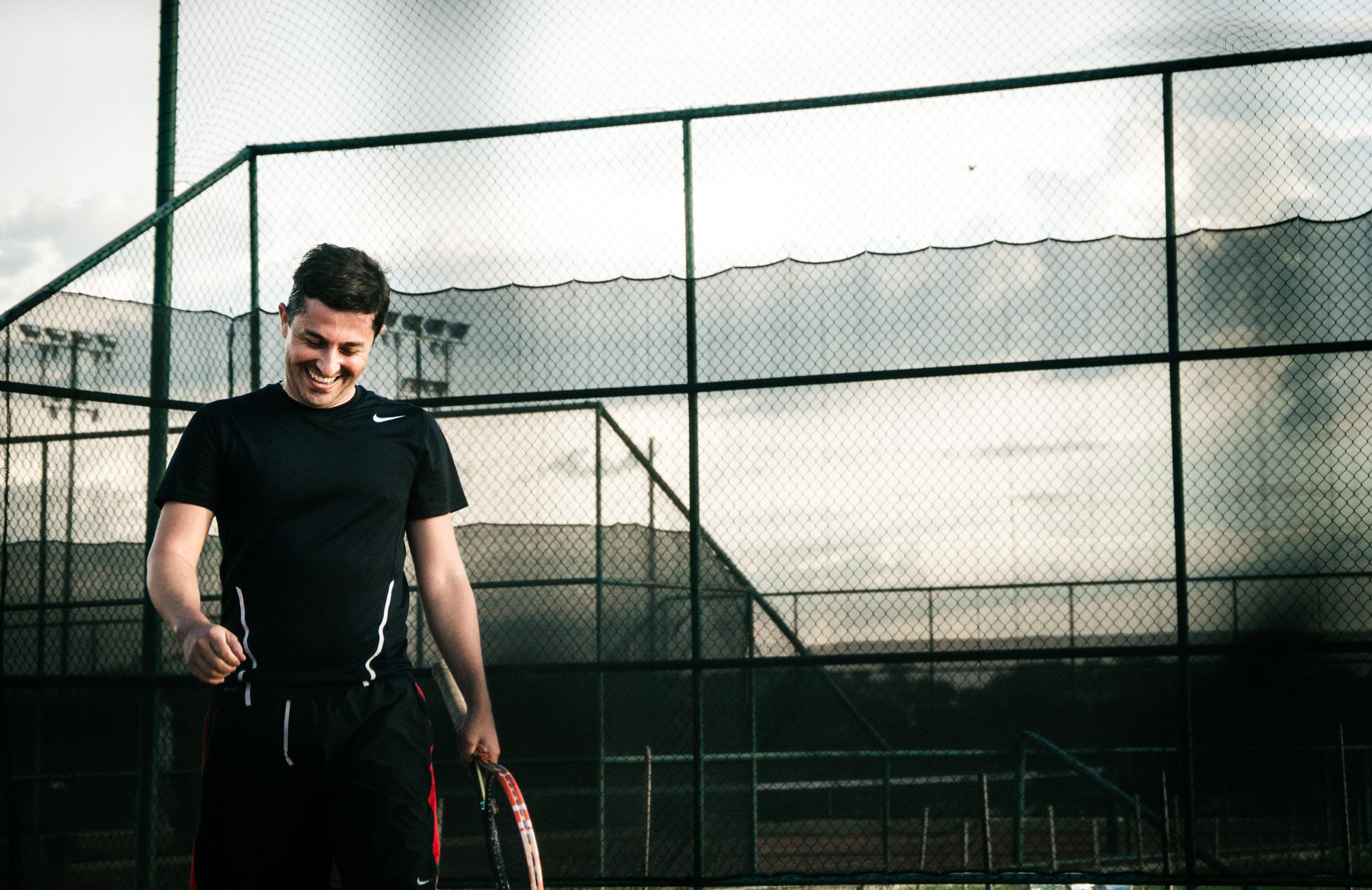 Man Wearing Black Nike Dri-fit Shirt Holding a Tennis Racket