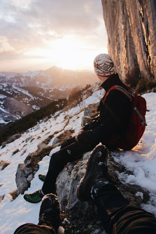 Selective Focus Photography of Man Sitting Snow-capped Mountain