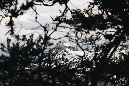 Long Shot Photo Of Snow Covered Mountain Peak Under Gray Cloudy Skies