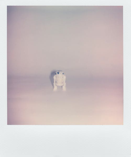 Polaroid Photo Of A Small Robot Toy In White Background