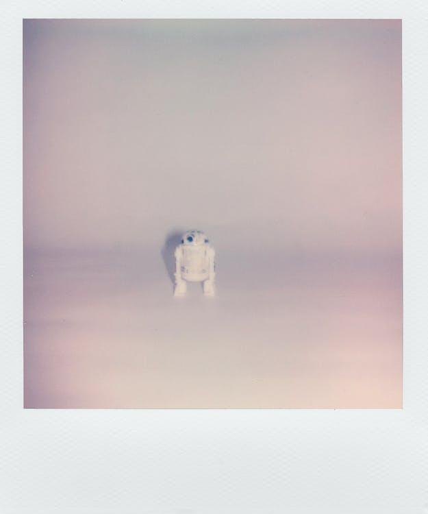Polaroid Photo Of A Small Robot Toy In White Background