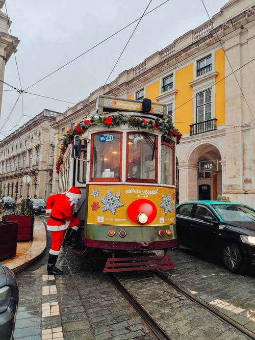 Santa Claus About to Enter Yellow Tram Beside Buildings