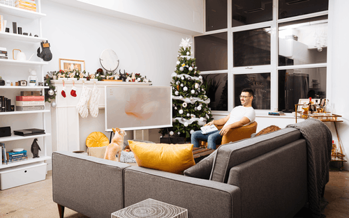 Man Wearing White Crew-neck T-shirt and Eyeglasses Holding Book While Sitting on Chair Near Christmas Tree in Living Room