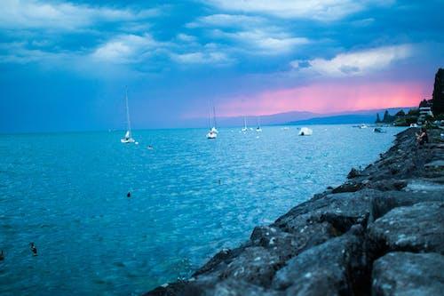 Foto d'estoc gratuïta de barques, capvespre, mar, núvols