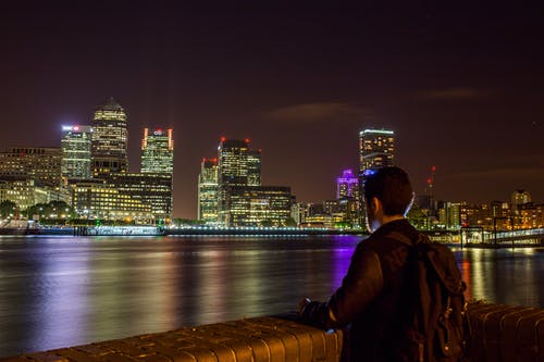 Man in Black Jacket Looking at the City