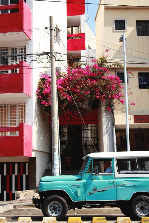 Blue Car Parked Beside Red and White Concrete Building