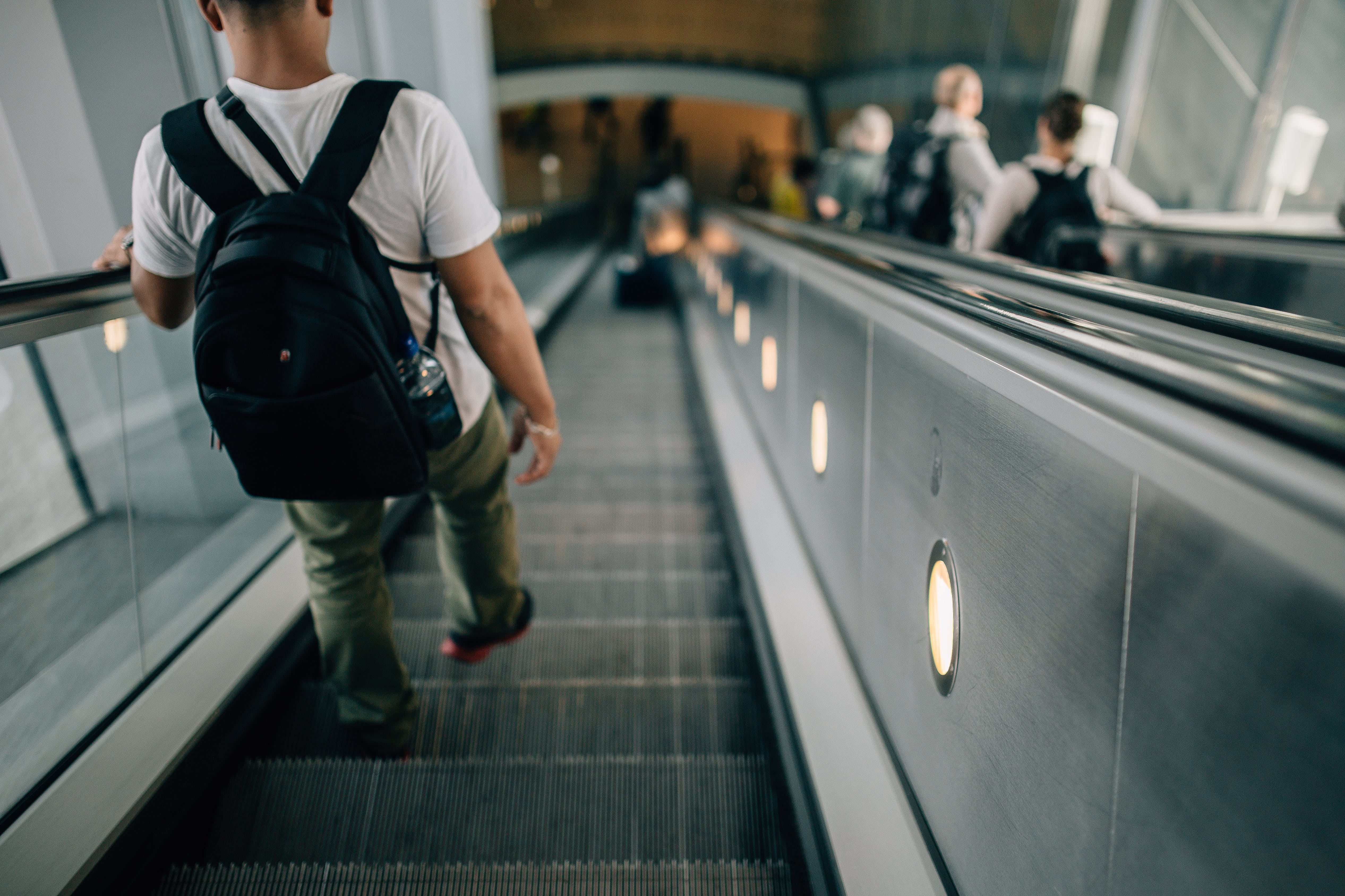 Person Wearing Black Backpack Riding Down the Escalator