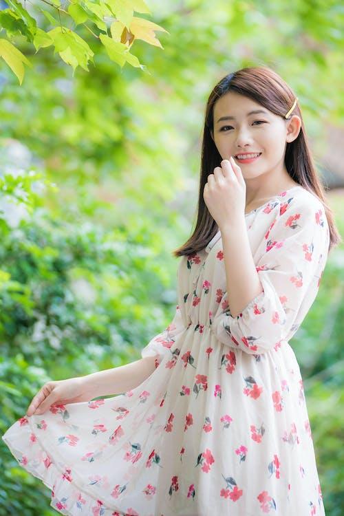 女人穿着白色和粉红色的花卉长袖连衣裙的浅焦点照片