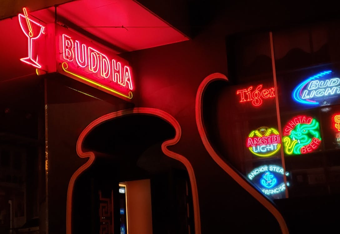 Red and White Buddha Neon Lights Sign during Night Time