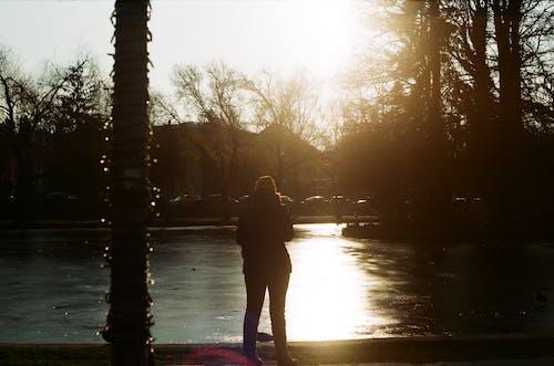 Woman Standing Near Lake during Sunrise