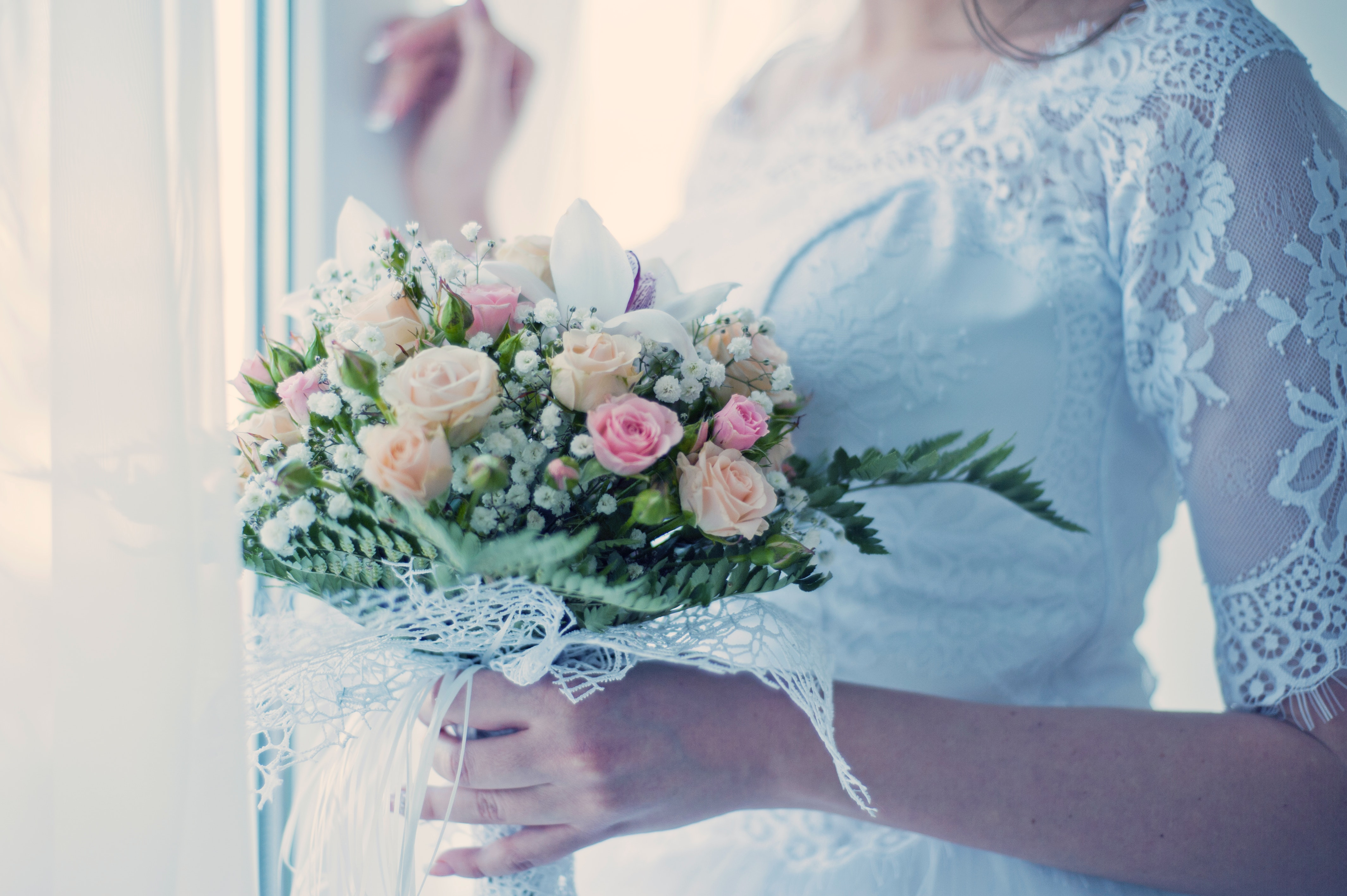 Woman in White Wedding Dress Holding a Bouquet of Flowers ...