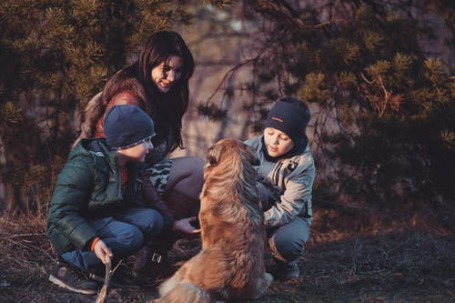 Three People Crouching in Front of Sitting Dog