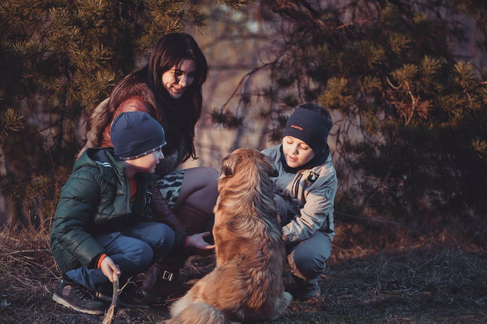 Mother and children in front of a dog. | Photo: Pexels