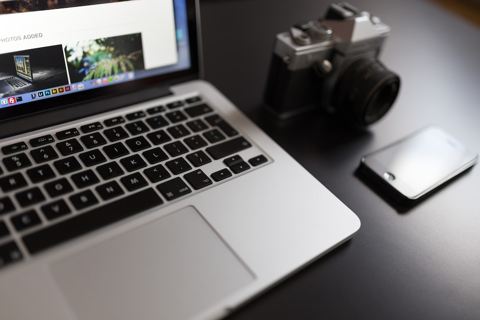 Silver Laptop Computer Beside of White and Black Camera and Black Iphone