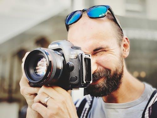 Man Wearing Gray Crew Neck Shirt Taking Photo Using Black Canon Camera
