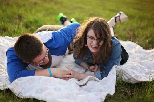 Two Person Laying on White Mat