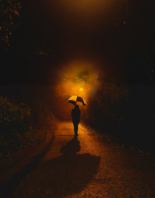 Person in Black Jacket Holding Yellow Umbrella Walking on Road during Night Time