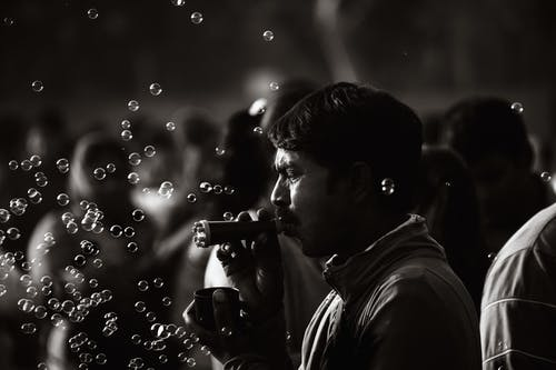Monochrome Photo Of Man Playing With Bubbles