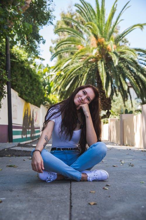Photo Of Woman Sitting On Concrete Ground