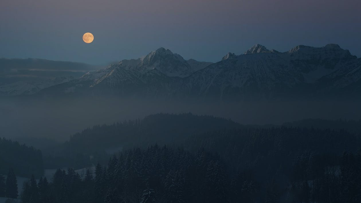 Silhouette of Mountains Covered With Light Mist Under The Full Moon