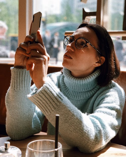 Woman Wearing Light-green Turtleneck Sweater and Eyeglasses Using Phone While Sitting Near Brown Wooden Table Beside Glass Wall