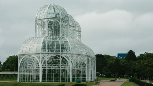 Wide Angle Shot Of White Greenhouse In The Middle of A Park