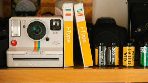 White Polaroid Land Camera Beside Photo Paper Boxes and Photo Films
