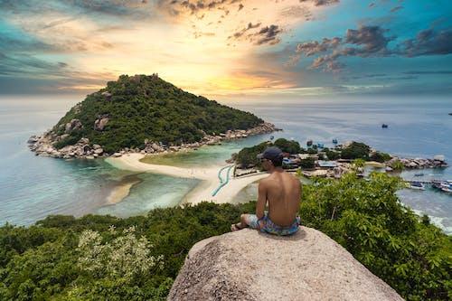岩の上に座っている上半身裸の男