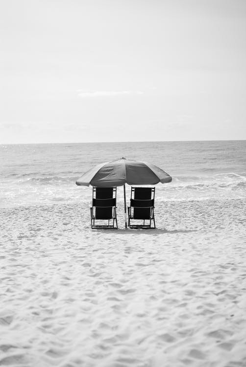 Grayscale Photography of Two Armchairs Near Body of Water