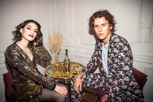 Man Wearing Floral Suit and Woman Wearing Shiny Dress