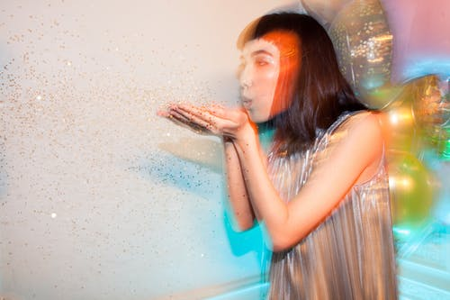 Woman Blowing Glitters