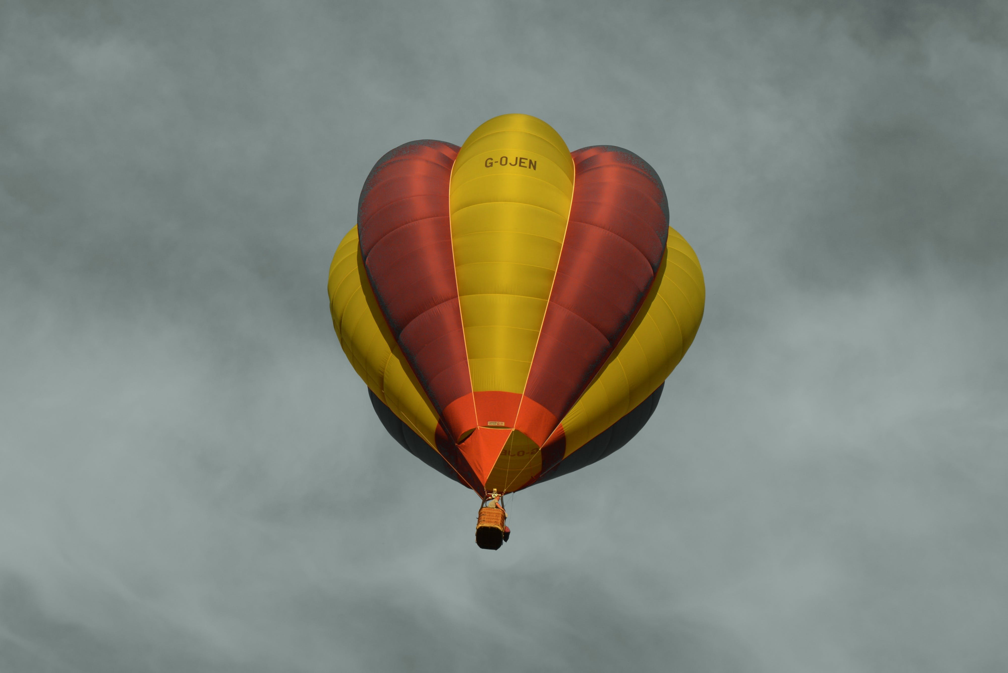 Red and Yellow Hot Air Balloon Under Sea of Clouds