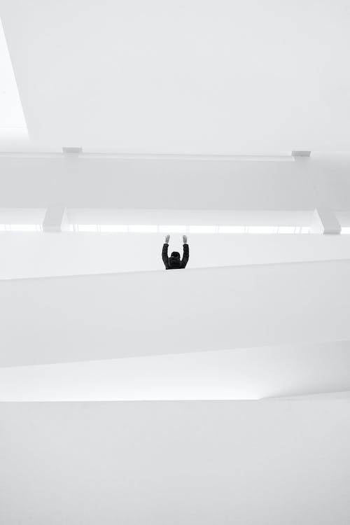 Person Raising Both Hands Inside Building