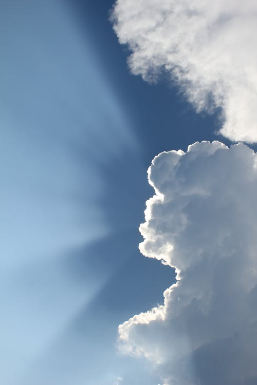 Sun Shining Behind Clouds in Blue Sky